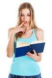 Lovely confused girl reading a book royalty free stock photography