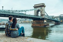 Lovely cople sitting on the beach and lookin at bridge Stock Photos