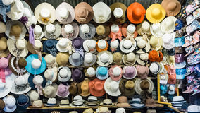Lovely corlorful caps, hats, and other headdress on wall in shop Royalty Free Stock Photo