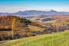 Lovely countryside in autumn. Village in the nearest mountain and mountain ridge with high peak in the distance. sunny weather royalty free stock photo