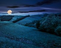Lovely countryside with grassy hills at night. In full moon light. beautiful nature of Carpathian mountains in springtime Royalty Free Stock Image