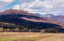 Lovely countryside landscape in springtime. Mountain with snowy top in the distance. village at the foot of the mountain royalty free stock photography
