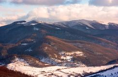 Lovely countryside in winter afternoon. Beautiful mountainous area with forested hills with snowy tops Stock Photos