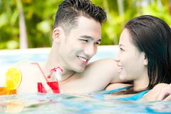 Lovely couple. Young couple spending time together in swimming pool with cocktails Stock Photos