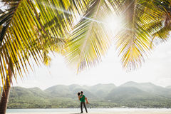 Lovely couple on the beach. With palms and mountain view with sunflare in vietnam Royalty Free Stock Photography