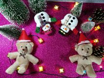 Lovely couple bear and snowman on pink gliter background near ornament lighting bulb at silent night, holy night, Merry Chr royalty free stock photo