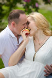 Lovely couple biting apple on picnic Royalty Free Stock Photography