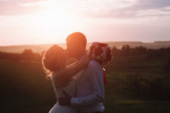 Lovely couple, bride and groom posing in field during sunset, lifestyle. Young beautiful wedding couple hugging in a field.Lovely couple, bride and groom posing Royalty Free Stock Photography