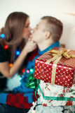 Lovely couple celebrating Christmas eve with present gifts Stock Photos