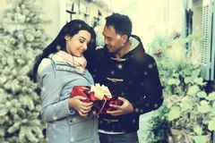 Lovely couple with a Christmas gift standing in the street Stock Images