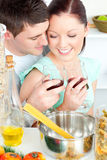 Lovely couple clinking glasses while cooking pasta Stock Photography