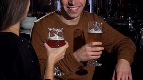 Lovely couple clinking their beer glasses, celebrating anniversary at restaurant. Cropped shot of a man and his girlfriend enjoying tasty craft beer stock video