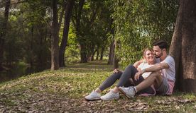 A lovely couple cuddling in a park in the morning stock photo