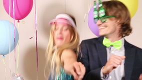 Lovely couple dancing wearing funny props. Lovely young couple dancing wearing funny props in photo booth stock footage