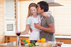 Lovely couple drinking red wine while kissing Royalty Free Stock Photography