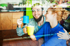 Lovely couple drinking tea together and talking. View through the window stock images