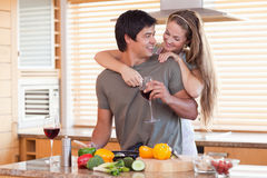 Lovely couple drinking wine while hugging Stock Images