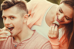 Lovely couple eating cupcakes. Stock Photo