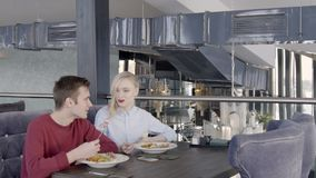 Lovely couple is eating salad in restaurant with stylish interior, slow motion. Blond woman in blue shirt and man in red jumper are sitting on velvet sofa at stock video