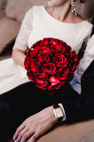 Lovely couple elegant bride and stylish groom resting on beige sofa together. Beautiful round bouquet of red roses flowers, shine Stock Photo