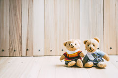 Lovely couple embrace bear sit on wooden table. Stock Photo