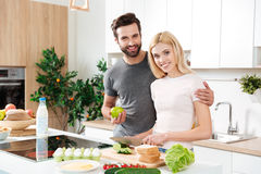 Lovely couple embracing each other in their kitchen royalty free stock photography