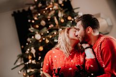 couple enjoying christmas and opening presents. Couple kissing in front of the christmas tree stock image