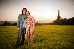 Lovely couple flirt in field on sunset Stock Photo