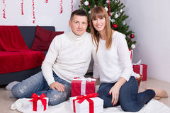 Lovely couple with gifts in front of Christmas tree Royalty Free Stock Photography
