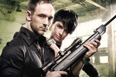 Lovely couple with gun in factory stock photography