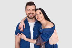 Lovely couple have warm cuddle, pose for family portrait, smile joyfully, have good relationships. Affectionate brother embraces. His sister isolated over white stock photography