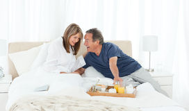 Lovely couple having breakfast in their bed Royalty Free Stock Images