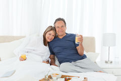 Lovely couple having breakfast in their bed Stock Image
