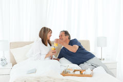 Lovely couple having breakfast in their bed Stock Photography
