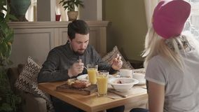 Lovely couple having breakfast together. Beautiful couple is spending their morning time eating breakfast together. Cereal and smoothies on table stock video