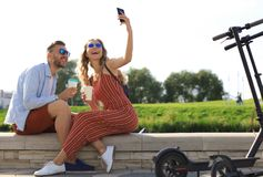 Free Lovely Couple Having Fun Driving Electric Scooter Through The City, Having A Break, Taking Selfie Royalty Free Stock Image - 161051996