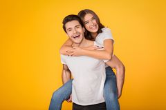 Lovely couple having fun, man piggybacking his girlfriend. Lovely couple having fun, men piggybacking his girlfriend over yellow background royalty free stock photography