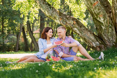 Lovely couple having a pleasant time eating fruits in the park Stock Images