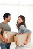 Lovely couple holding cardboards. In their living-room during their removal Royalty Free Stock Photo