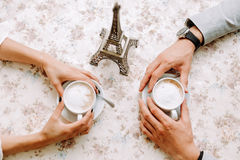 Lovely couple holding cup of coffee in hands Stock Photos