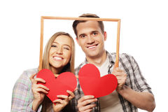 Lovely couple holding frame and red hearts Royalty Free Stock Photo
