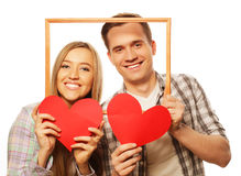 Lovely couple holding frame and red hearts Stock Image