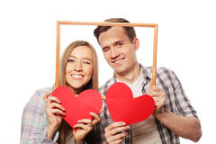 Lovely couple holding frame and red hearts Royalty Free Stock Photography