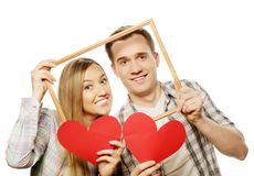 Lovely couple holding frame and red hearts Royalty Free Stock Images