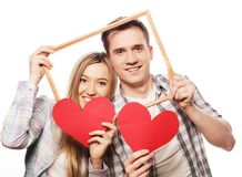 Lovely couple holding frame and red hearts Royalty Free Stock Photos