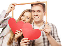 Lovely couple holding frame and red hearts Royalty Free Stock Image