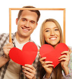 Lovely couple holding frame and red hearts Stock Photo