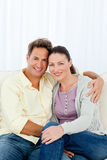 Lovely couple hugging sitting on the sofa Stock Photos