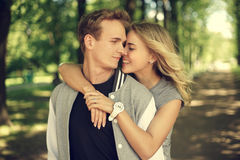 Lovely couple hugging in summer park. Happy young couple. Beautiful smiling blonde girl hugging her boyfriend from the back Stock Photo