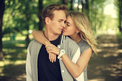 Lovely couple hugging in summer park. Happy young couple. Beautiful smiling blonde girl hugging her boyfriend from the back Stock Photography